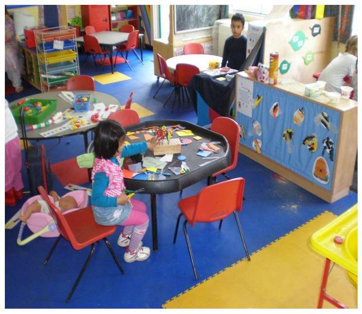 Auf diesem Bild sind zwei Kinder beim spielen auf einem blau gelben PVC Boden von FLOORWORK zu sehen.